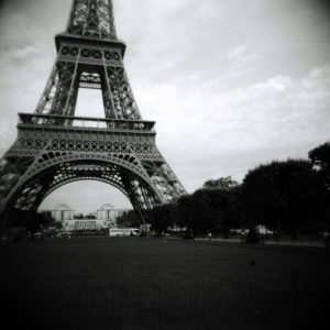 A low view of the Eiffel Tower from the street. It is in black and white