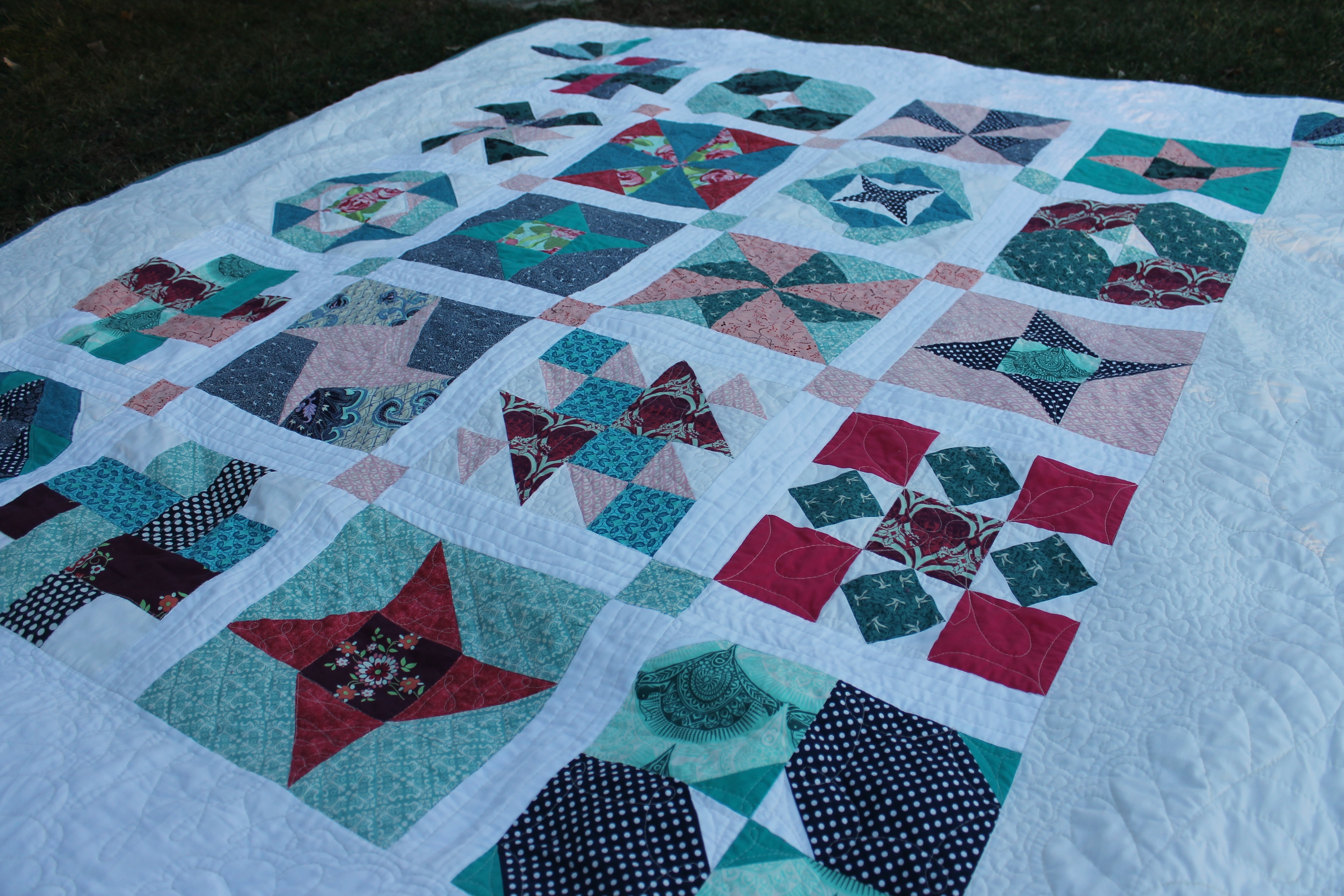 A Water Penny Sampler Quilt with turquoise and red variety of small squares on a white background
