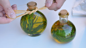 two orb shaped glass bottles with cork stoppers filled with oil and herbs