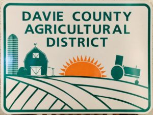 A metal sign with an illustrated field with a silo, barn, and tractor in green and a sun in orange. On the sign is writing that says Davie County Agricultural District