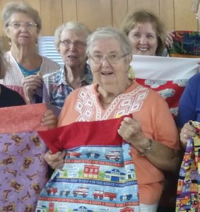 Extension and Community Association Volunteer Members holding pillow cases that were made during the Ryan's Case for Smiles event to make fun pillow cases for children in the hosptial